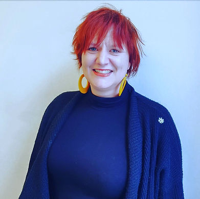 Picture of Andrea Geipel - a woman with red hair, blue eyes, big yellow earrings, a black sweater and a black jacket.