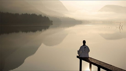 Man Meditating near a misty lake