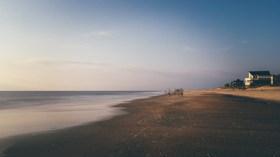 edge of a beach with a group of people walking along the shore