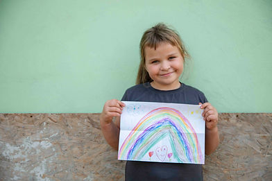 A 7-year-old girl stands in front of the plywood for her new home, holding a drawing she made of a rainbow.
