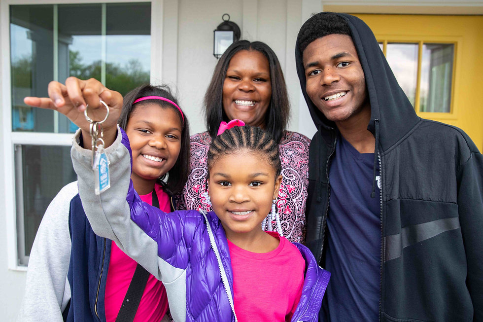A family with mother, two daughters (10 & 8) and son (16) are smiling and holding the key to their new Habitat for Humanity home.