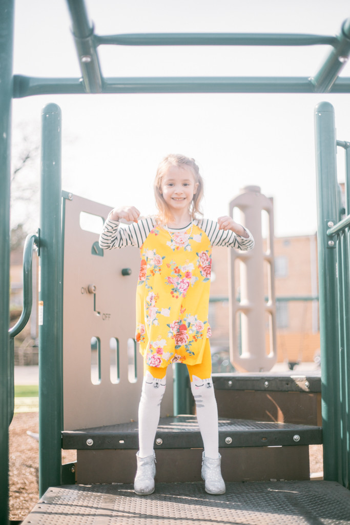 Little girl smiling and jumping during a family lifestyle photography session.