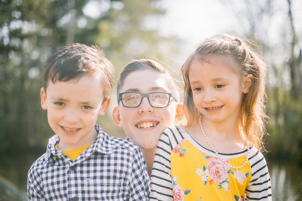Siblings smiling during a family lifestyle photography session.