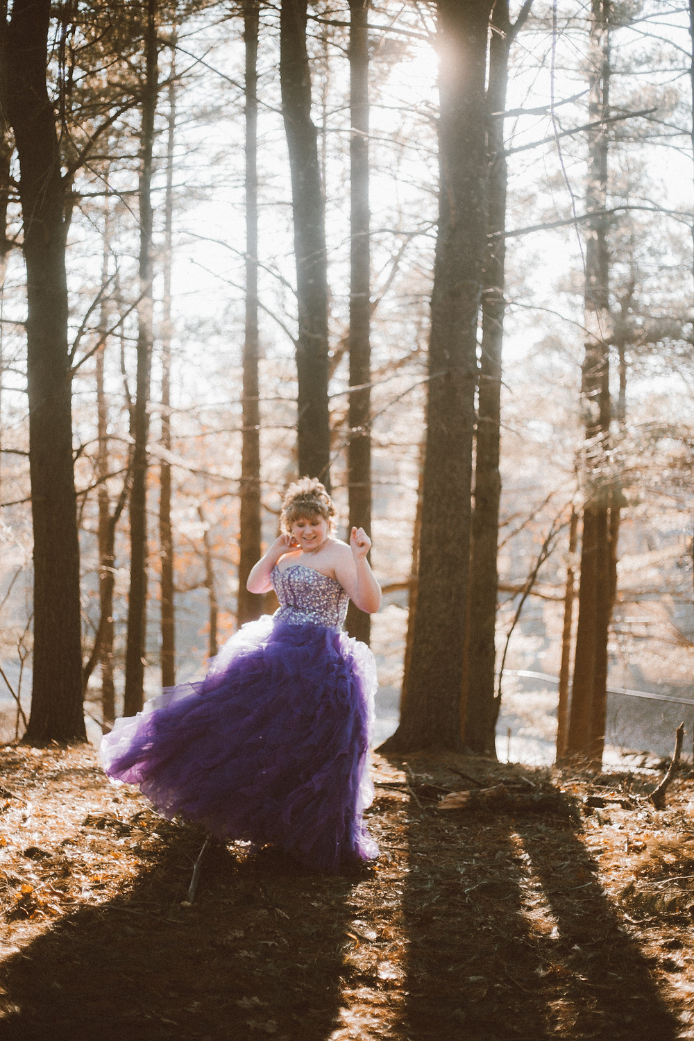 Teenage girl twirls in her prom dress in the woods. Lifestyle photography by Anna Gutermuth.