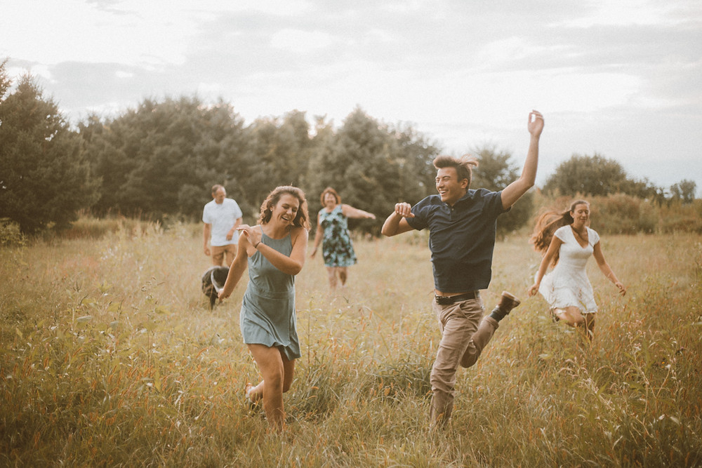 Family frolics in a field with their dog. Lifestyle family photography by Anna Gutermuth.