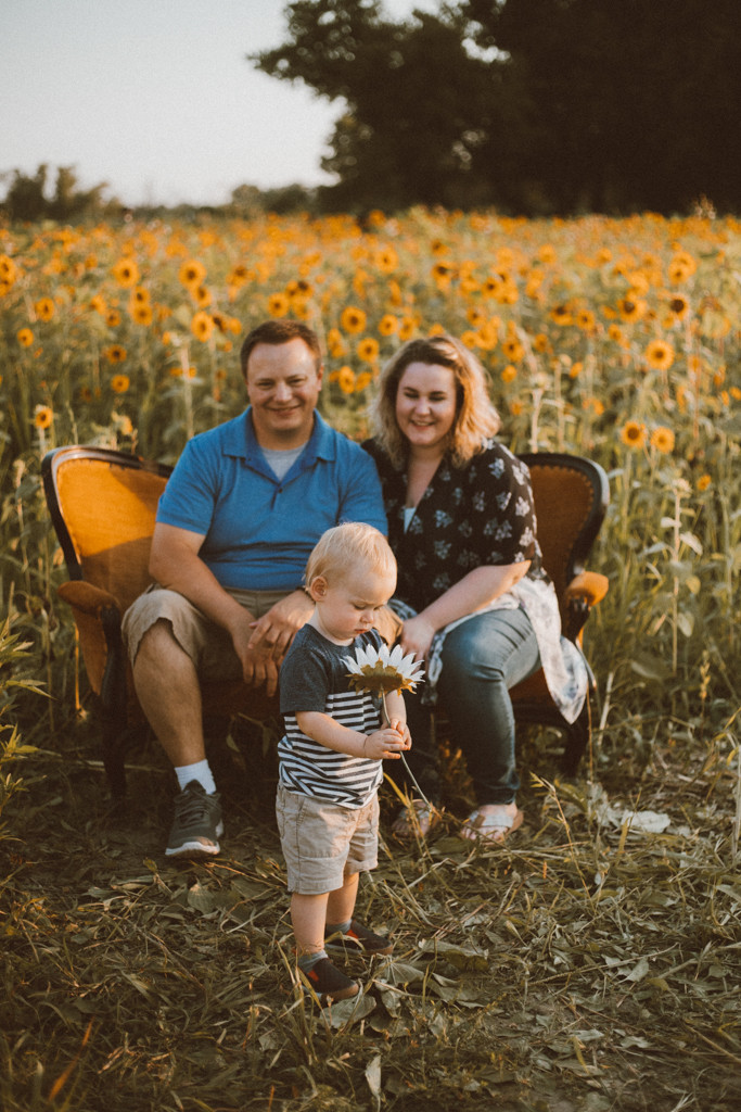Mom and boyfriend smile and little boy holding a flower. Lifestyle Photography by Anna Gutermuth.