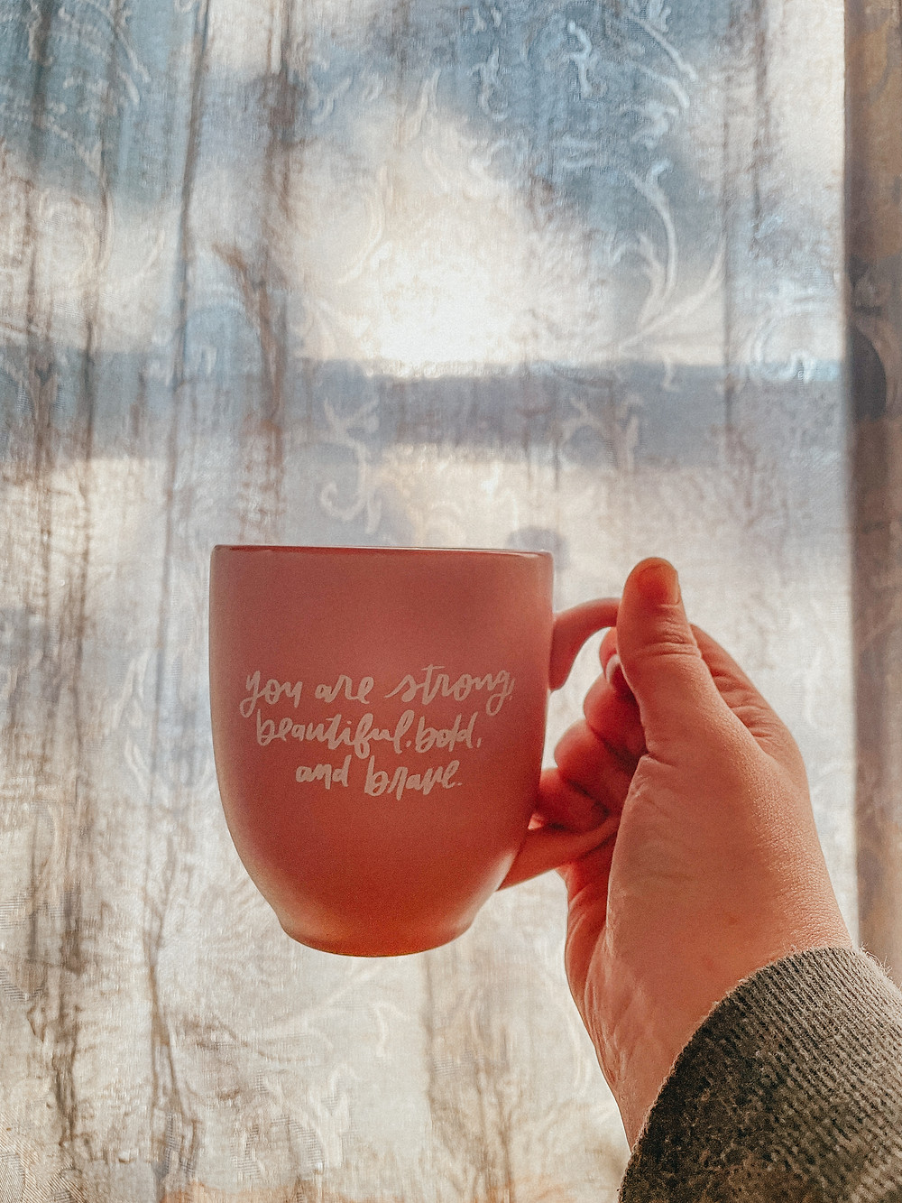 Cup of coffee in winter sunlight. Mug reads You are strong, beautiful, bold, and brave. Behind the scenes at Anna Gutermuth Photography.
