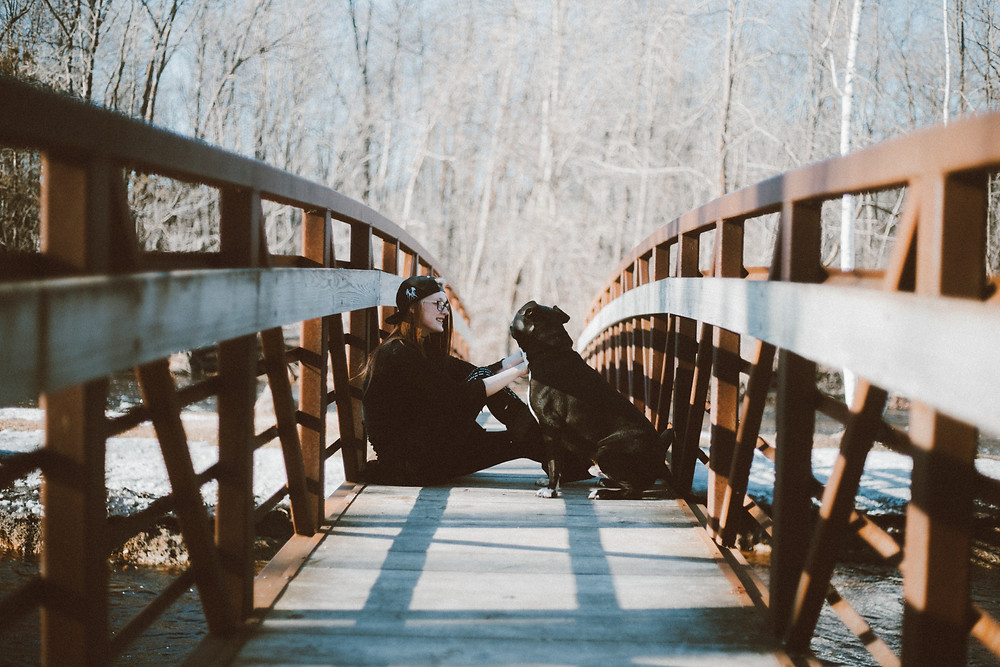 Red haired women sits on bridge across from a black pitbull dog during their lifestyle photography session.