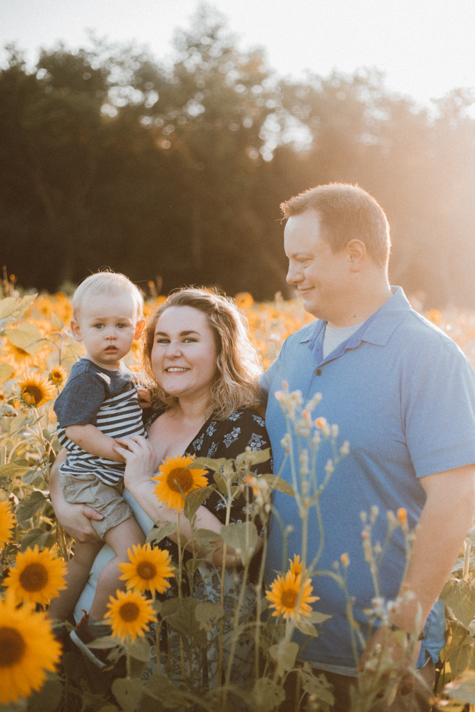 Family standing in sunflower field. Lifestyle Photography by Anna Gutermuth.