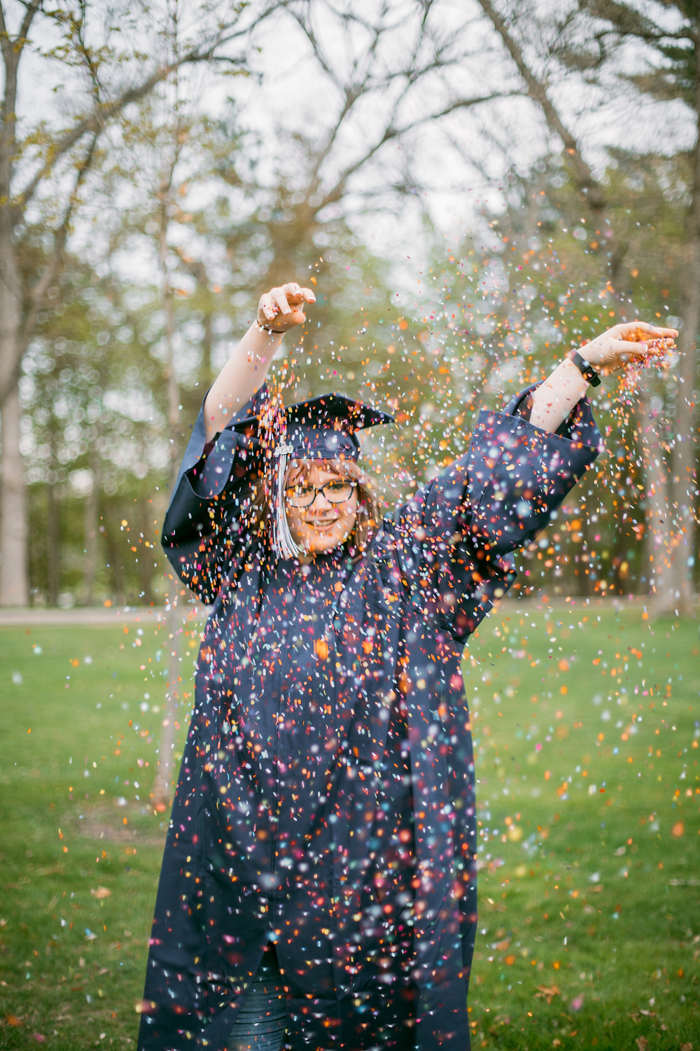 Class of 2020 Graduate throwing rainbow confetti. Lifestyle senior photography by Anna Gutermuth.