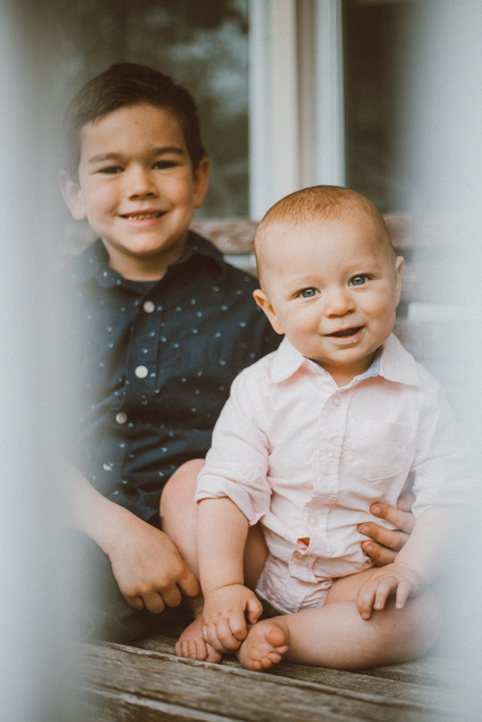 Big brother and little brother posing on the front porch of their new house. Lifestyle family photography in Trevor, WI.