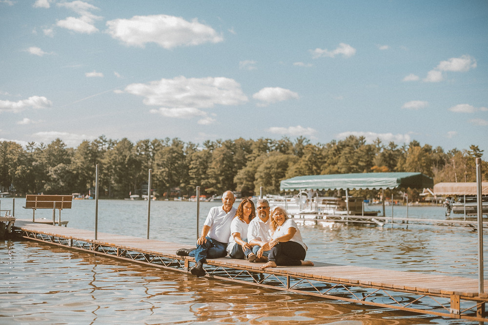 Family sitting on the dock. Lifestyle Photography by Anna Gutermuth.