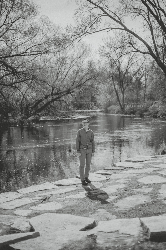 Teenage boy standing by the river during a family lifestyle photography session.