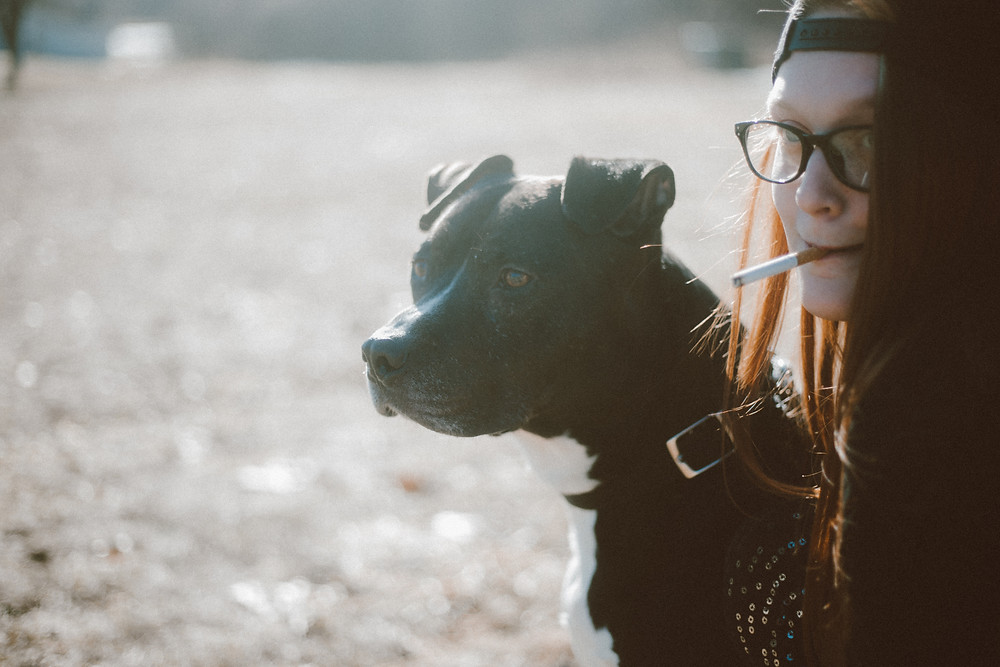 Black pitbull dog and red haired woman holding a cigarette in her mouth look off into the distance during their lifestyle photography session.
