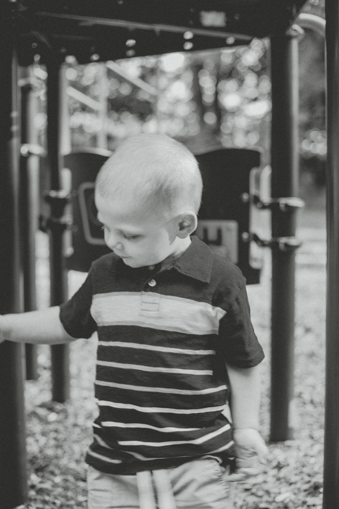 Boy on playground equipment. Lifestyle family photography by Anna Gutermuth.
