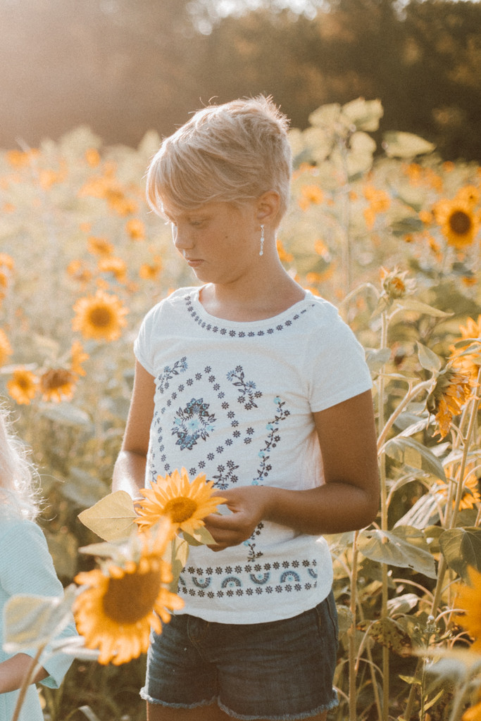 Girl looking at sunflowers. Lifestyle Photography by Anna Gutermuth.