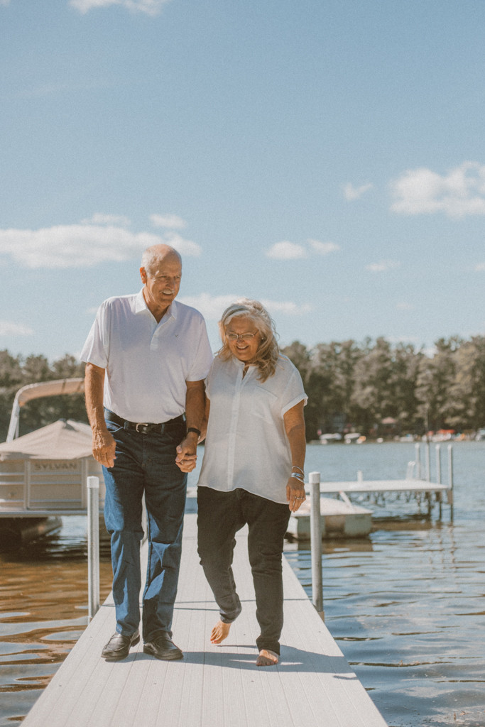 Couple walks hand-in-hand down the dock. Lifestyle Photography by Anna Gutermuth.