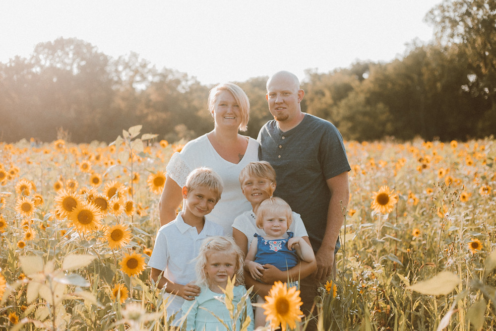 Family stands in sunflower field. Lifestyle Photography by Anna Gutermuth.