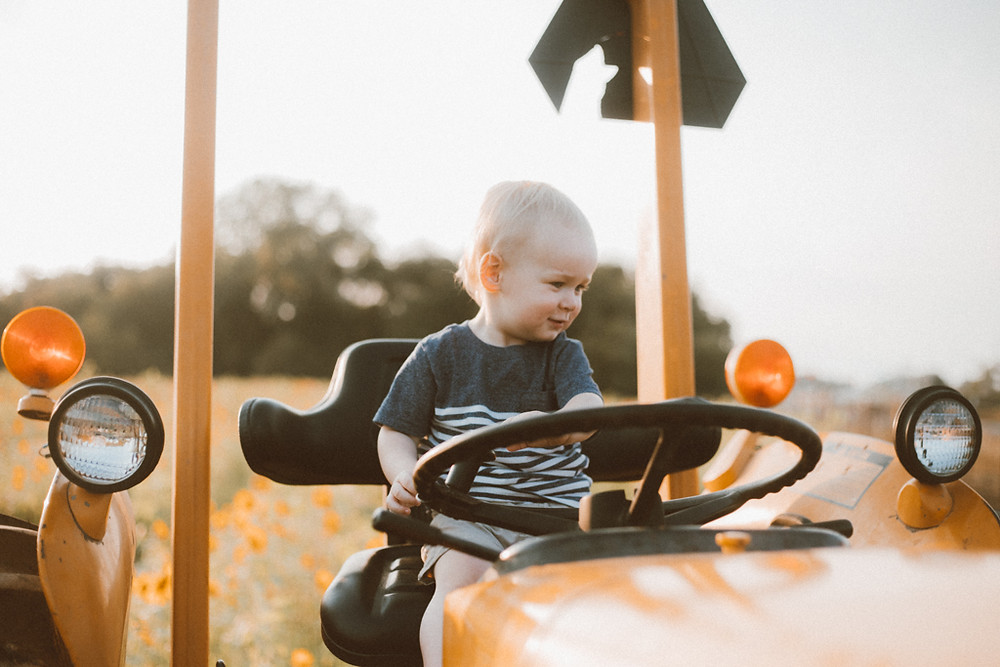 Little boy checks out a vintage tractor. Lifestyle Photography by Anna Gutermuth.