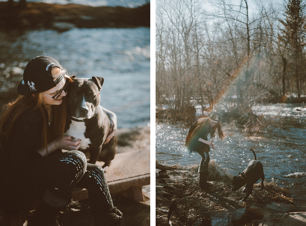 Red haired woman sits on a bench with black pitbull dog on leash  and wades into the river during their lifestyle photography session.