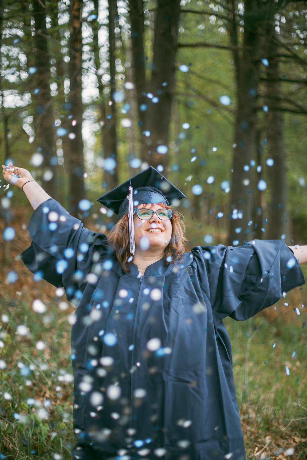 Class of 2020 Graduate throwing blue and silver confetti. Lifestyle senior photography by Anna Gutermuth.