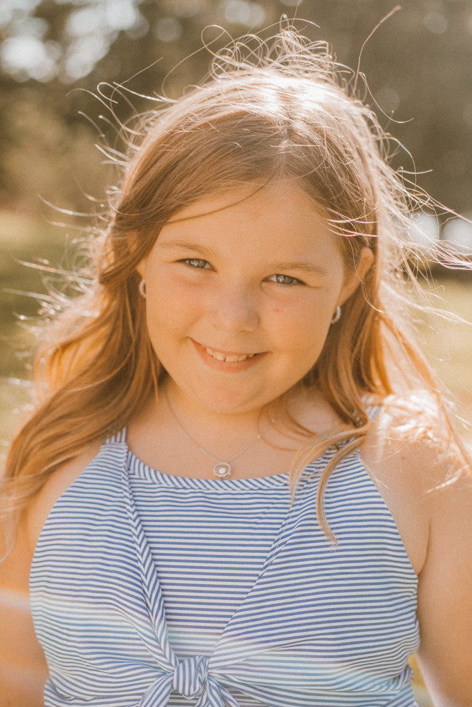 Little girl showing off her diamond necklace and earrings. Lifestyle Photography by Anna Gutermuth.