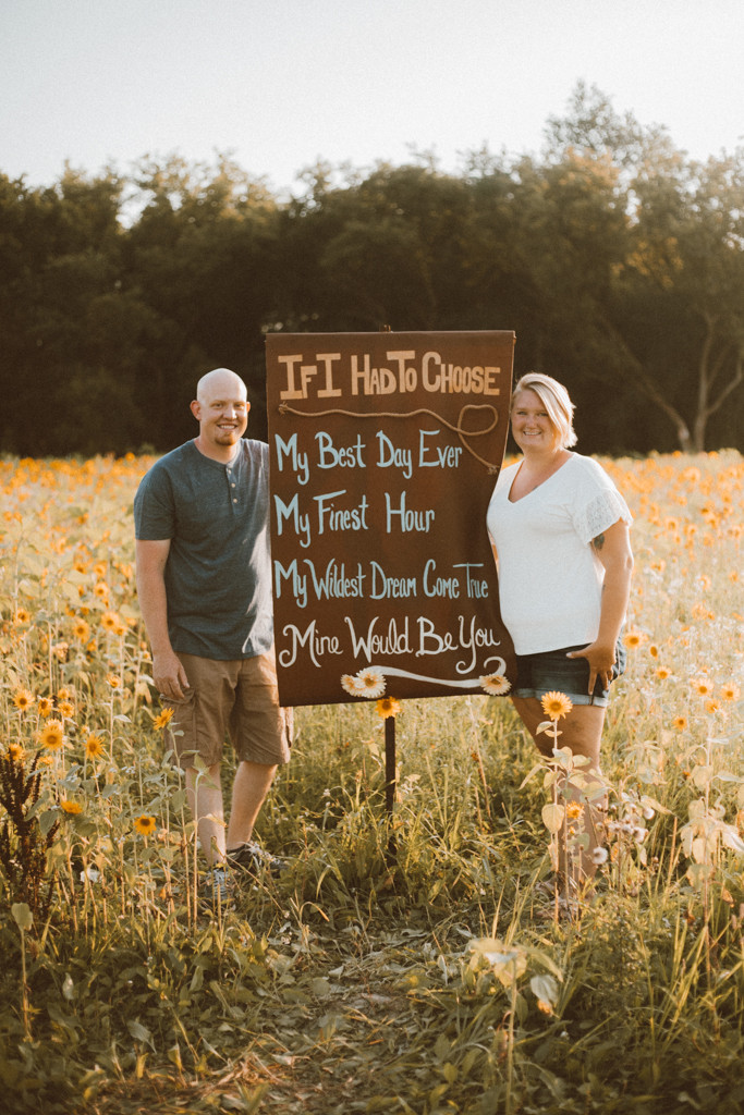 Mom and dad stand in front of a sign at the sunflower field. Lifestyle Photography by Anna Gutermuth.