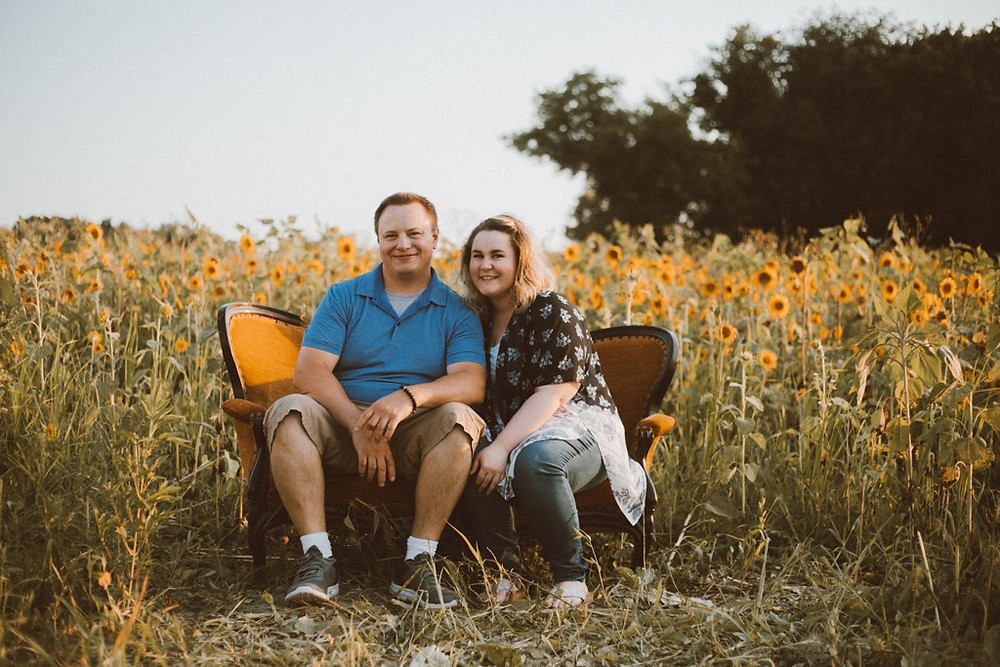 Couple sitting on couch in front of the sunflower field. Lifestyle Photography by Anna Gutermuth.