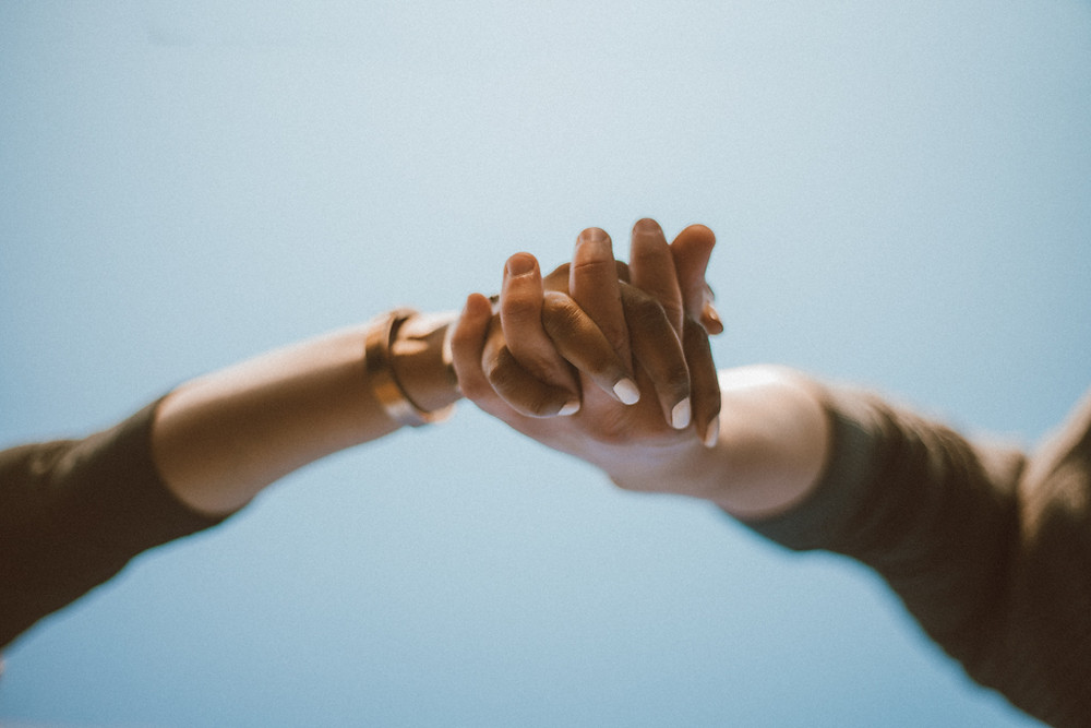 Couple holding hands against blue sky. Lifestyle engagement photography by Anna Gutermuth.