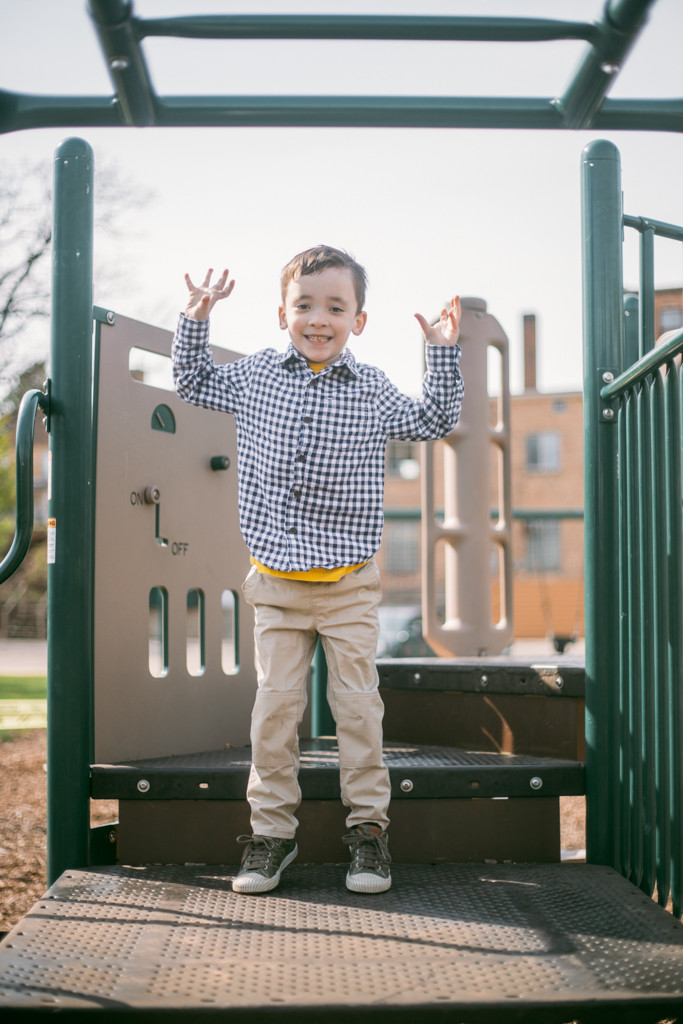 Little boy smiling and jumping during a family lifestyle photography session.