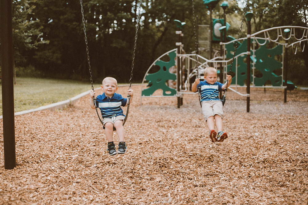 Brothers on swingset. Lifestyle family photography by Anna Gutermuth.