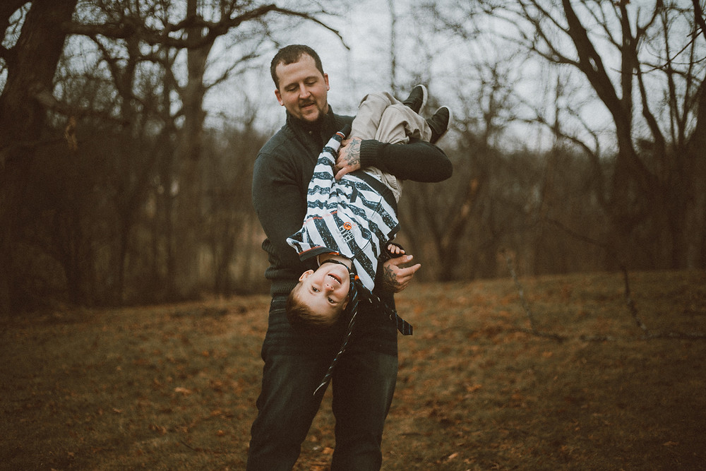 Dad, and son play in the backyard during their maternity lifestyle photography session.