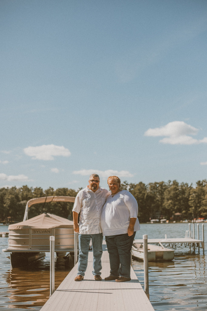 Couple stands on the dock by the lake. Lifestyle Photography by Anna Gutermuth.