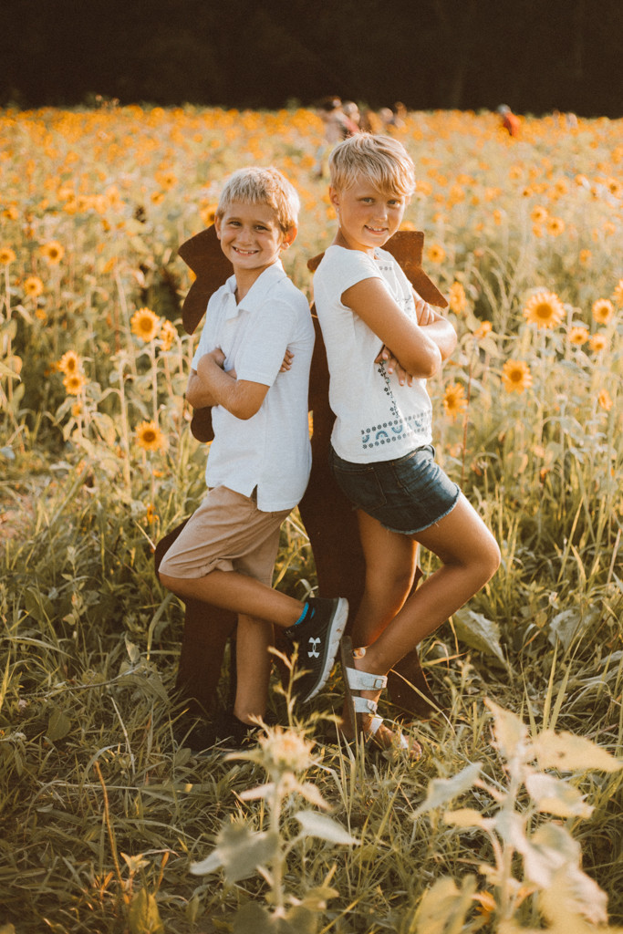 Older siblings strike a post in the sunflower field. Lifestyle Photography by Anna Gutermuth.