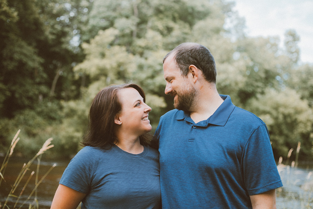 Mom and dad smiling at each other. Lifestyle family photography by Anna Gutermuth.