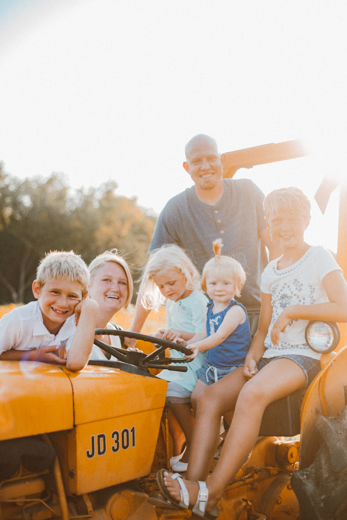 Family gathers around a vintage John Deere tractor. Lifestyle Photography by Anna Gutermuth.