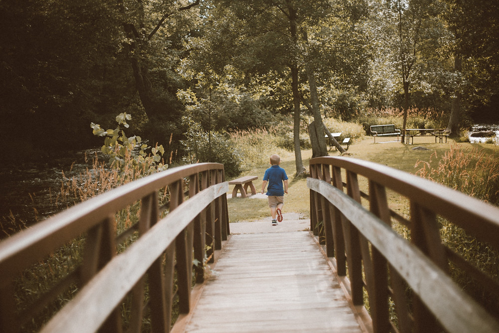 Boy runs across bridge. Lifestyle family photography by Anna Gutermuth.