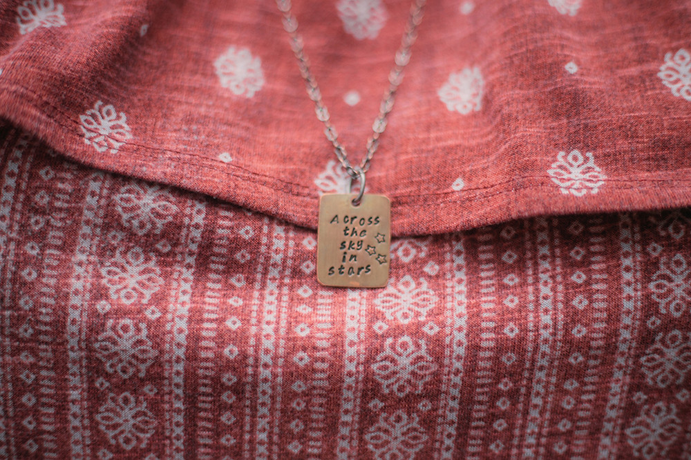 Necklace that reads across the sky in stars against a pink and white patterned shirt. Wisconsin Lifestyle Photography.