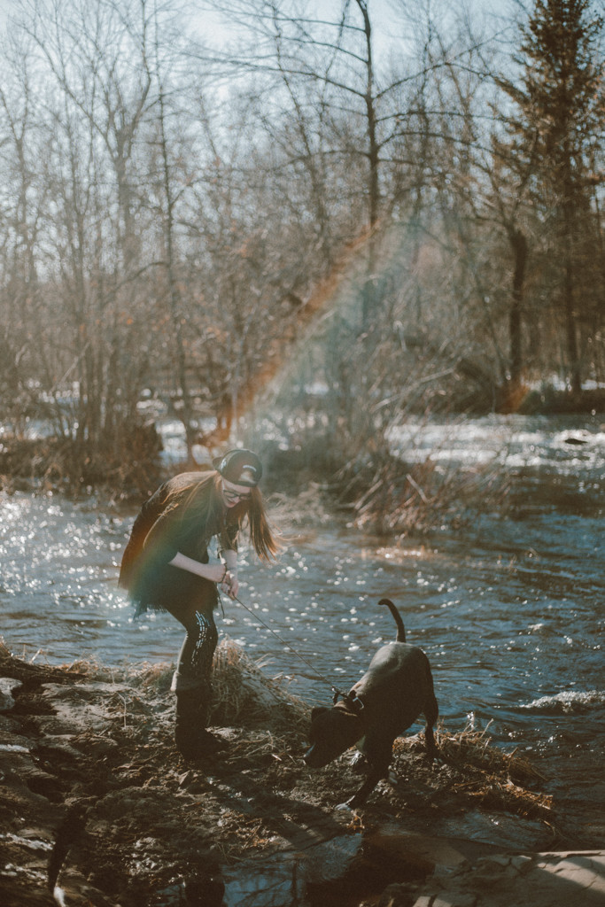 Girl and her pitbull dog stand by the river. Lifestyle photography by Anna Gutermuth.