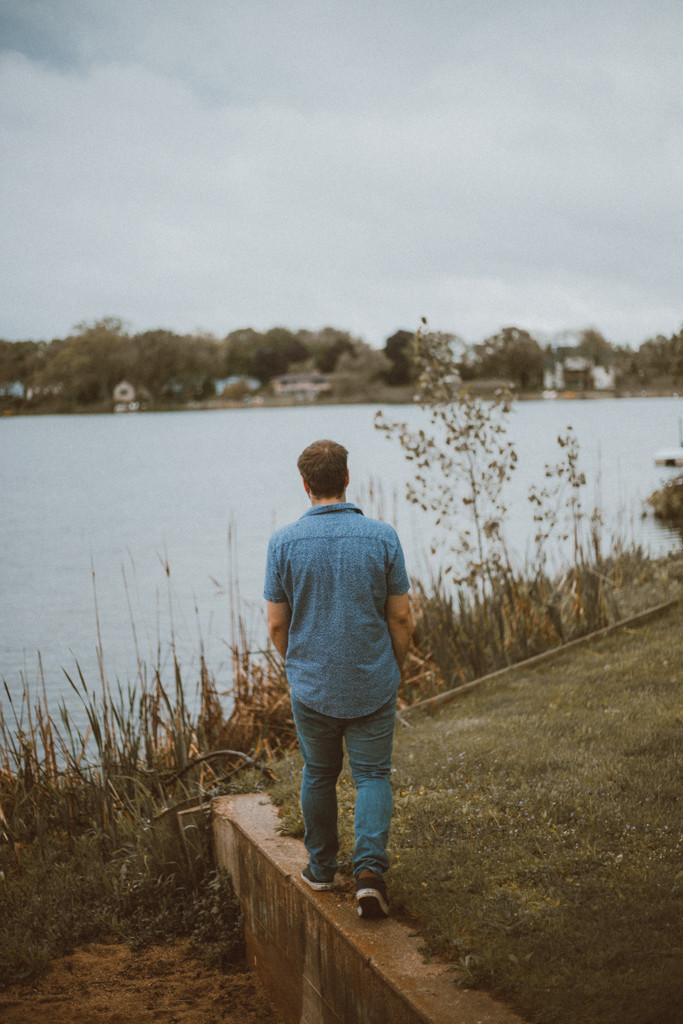 Dad walks along the wall at Rock Lake. Lifestyle family photography in Trevor, WI.