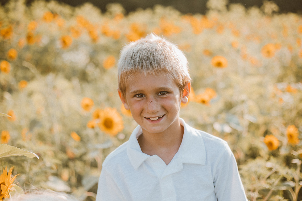 Boy standing in sunflower field. Lifestyle Photography by Anna Gutermuth.