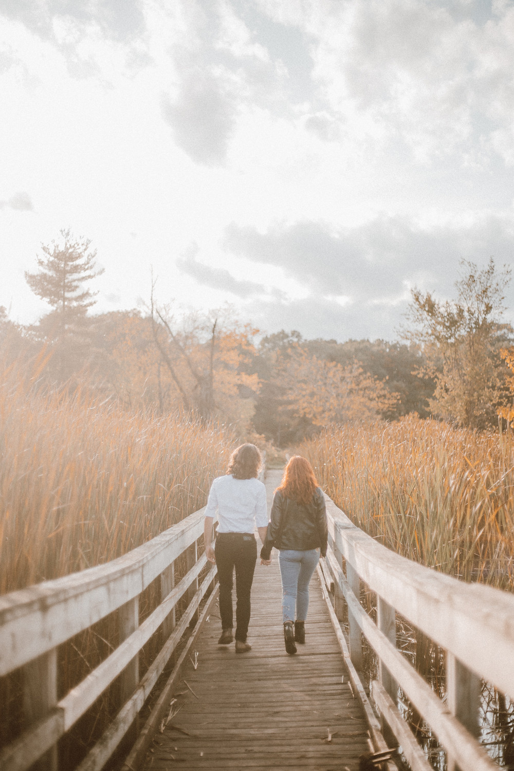 Couple walks down bridge holding hands. Lifestyle engagement photography by Anna Gutermuth.