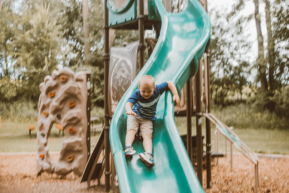 Little boy going down the big slide. Lifestyle family photography by Anna Gutermuth.