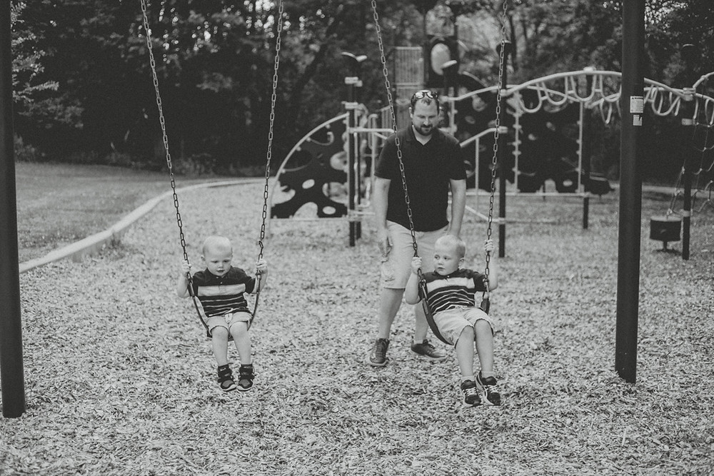 Dad pushes kids on swings. Lifestyle family photography by Anna Gutermuth.