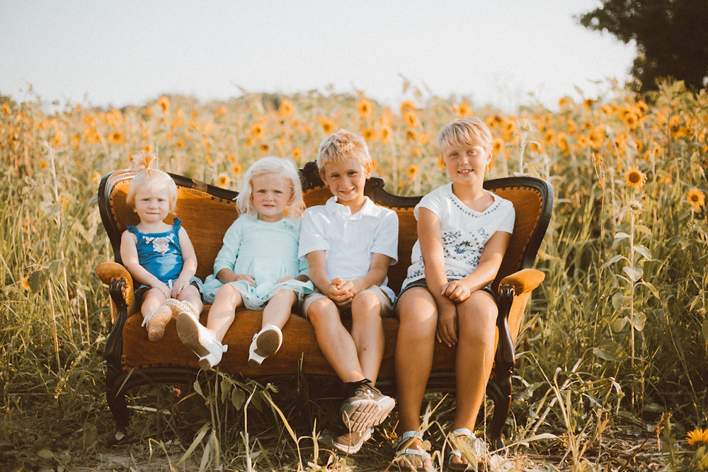 Siblings sit on a couch in front of the sunflower field. Lifestyle Photography by Anna Gutermuth.