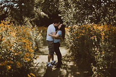 couple kissing in a field of yellow black eyed susan flowers