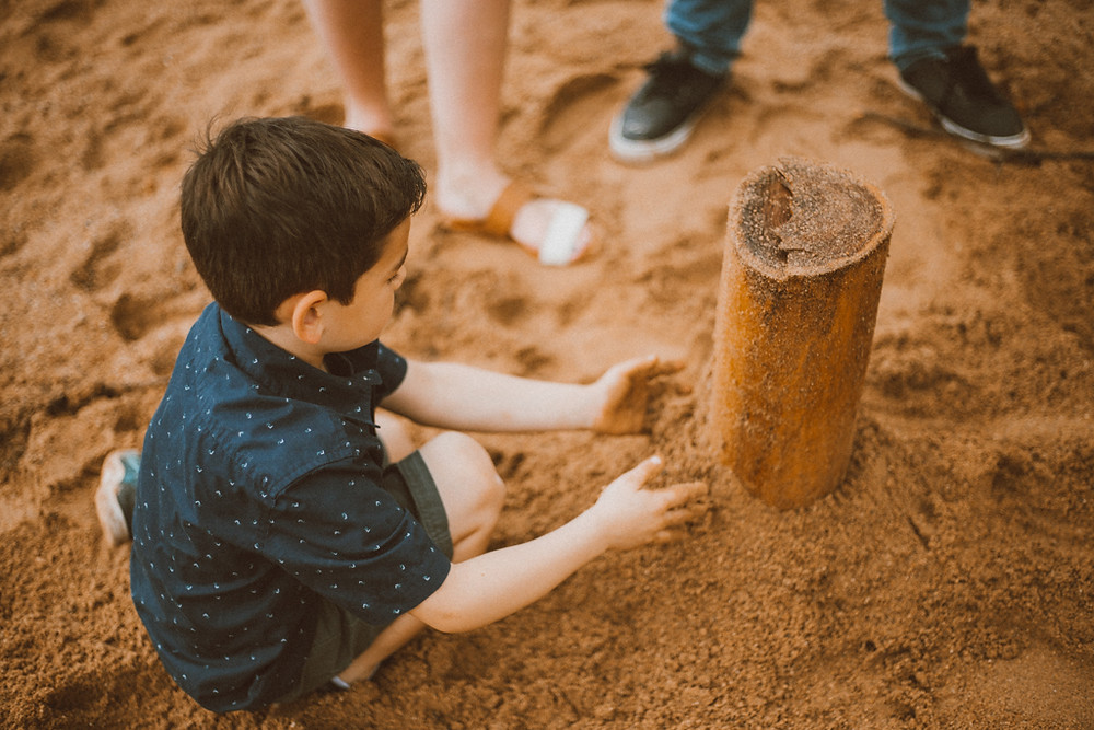 Big brother plays in the sand at Rock Lake. Lifestyle family photography in Trevor, WI.