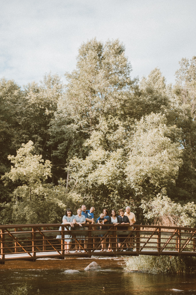 Family standing on bridge. Lifestyle family photography by Anna Gutermuth.