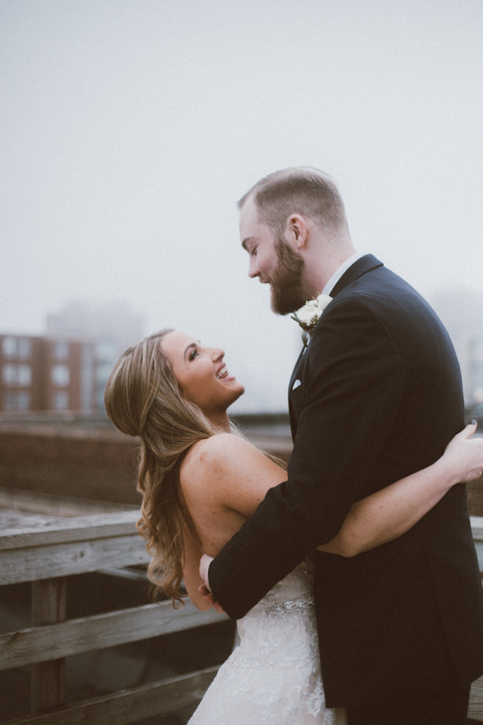 Bride and groom share a moment on a foggy rooftop before their ceremony. Wedding photography by Anna Gutermuth.