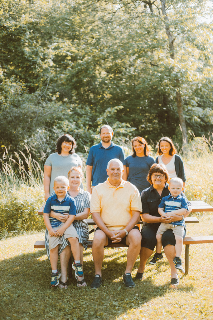 Family sits at picnic table. Lifestyle family photography by Anna Gutermuth.